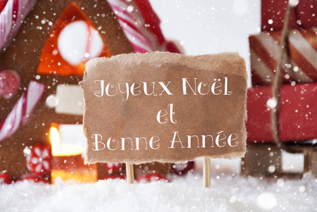 bonne: Gingerbread House In Snowy Scenery As Christmas Decoration. Sleigh With Christmas Gifts And Snowflakes. Label With French Text Joyeux Noel Et Bonne Annee Means Merry Christmas And Happy New Year