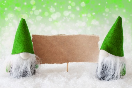 gnomos: Christmas Greeting Card With Two Green Gnomes. Sparkling Bokeh And Natural Background With Snow. Copy Space For Advertisement