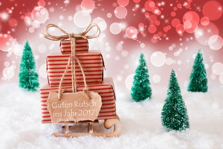 ins: Sleigh Or Sled With Christmas Gifts Or Presents. Snowy Scenery With Snow And Trees. Red Sparkling Background With Bokeh Effect. Label With German Text Guten Rutsch Ins Jahr 2017 Means Happy New Year