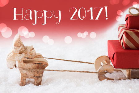 christmassy: Moose Is Drawing A Sled With Red Gifts Or Presents In Snow. Christmas Card For Seasons Greetings. Red Christmassy Background With Bokeh Effect. English Text Happy 2017 For Happy New Year