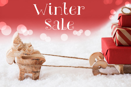 christmassy: Moose Is Drawing A Sled With Red Gifts Or Presents In Snow. Christmas Card For Seasons Greetings. Red Christmassy Background With Bokeh Effect. English Text Winter Sale Stock Photo