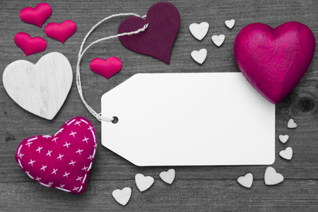 hot spot: Label With Copy Space For Advertisement. Pink Textile Hearts On Wooden Gray Background. Retro Or Vintage Style. Black And White Image With Colored Hot Spot.