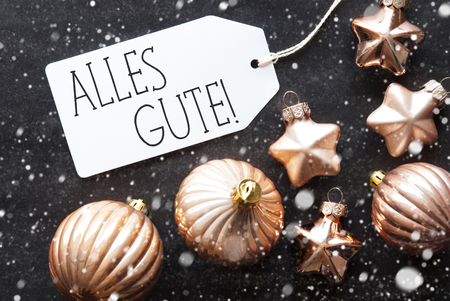 best wishes: Label With German Text Alles Gute Means Best Wishes. Bronze Christmas Tree Balls On Black Paper Background With Snowflakes. Christmas Decoration Or Texture. Flat Lay View