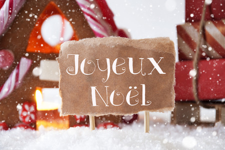 joyeux: Gingerbread House In Snowy Scenery As Christmas Decoration. Sleigh With Christmas Gifts Or Presents And Snowflakes. Label With French Text Joyeux Noel Means Merry Christmas