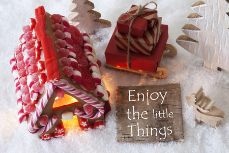 Label With English Quote Enjoy The Little Things. Gingerbread House On Snow With Christmas Decoration Like Trees And Moose. Sleigh With Christmas Gifts Or Presents.