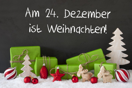 German Text Am 24. Dezember Ist Weihnachten Means December 24th Is Christmas Eve. Green Gifts With Decoration Like Tree, Moose Or Red Christmas Tree Ball. Black Cement Wall As Background With Snow. Stock Photo