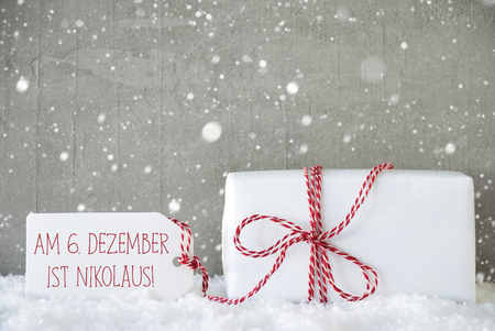 nikolaus: One Christmas Present On Snow. Cement Wall As Background With Snowflakes. Modern And Urban Style. Card For Seasons Greetings. Label With German Text Am 6. Dezember Ist Nikolaus Means Nicholas Day