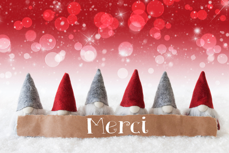 christmassy: Label With French Text Merci Means Thank You. Christmas Greeting Card With Red Gnomes. Sparkling Bokeh And Christmassy Background With Snow And Stars.