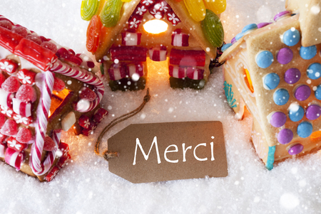 merci: Label With French Text Merci Means Thank You. Colorful Gingerbread House On Snow And Snowflakes. Christmas Card For Seasons Greetings