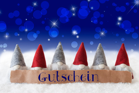 Label With German Text Gutschein Means Voucher. Christmas Greeting Card With Gnomes. Sparkling Bokeh And Blue Background With Snow And Stars. Stock Photo