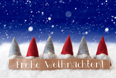 Label With German Text Frohe Weihnachten Means Merry Christmas. Christmas Greeting Card With Gnomes. Blue Background With Snowflakes Stock Photo