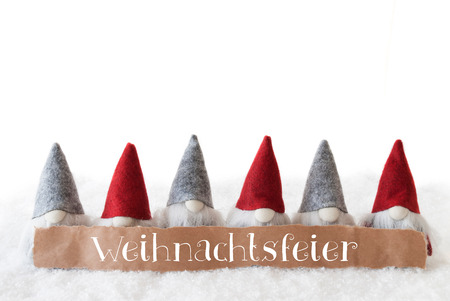 Label With German Text Weihnachtsfeier Means Christmas Party. Christmas Greeting Card With Gnomes. Isolated White Background With Snow.
