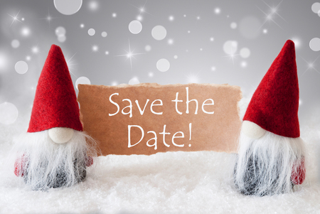 english text save the date christmas greeting card with two red gnomes sparkling bokeh