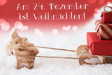 christmassy: Moose Is Drawing A Sled With Red Gifts Or Presents In Snow. Red Christmassy Background With Bokeh Effect. German Am 24. Dezember Ist Weihnachten Means Christmas Eve