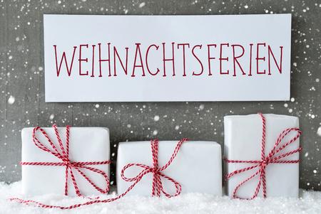 Label met Duitse tekst Frohe Weihnachten Betekent Vrolijk kerstfeest. Drie Kerst cadeaus of presenteert op sneeuw. Cement wand als achtergrond met sneeuwvlokken. Moderne En Urban Style. Stockfoto