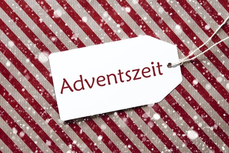 advent season: One Label On A Red And Brown Striped Wrapping Paper. Textured Background With Snowflakes. Tag With Ribbon. German Text Adventszeit Means Advent Season