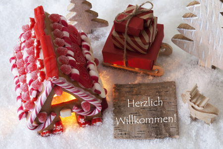 willkommen: Label With German Text Herzlich Willkommen Means Welcome. Gingerbread House On Snow With Christmas Decoration Like Trees And Moose. Sleigh With Christmas Gifts Or Presents.