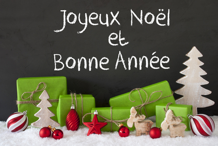 bonne: French Text Joyeux Noel Et Bonne Annee Means Merry Christmas And Happy New Year. Green Gifts With Christmas Decoration Like Tree, Moose Or Red Balls. Black Cement Wall As Background With Snow.