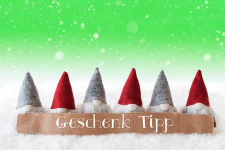 Label With German Text Geschenk Tipp Means Gift Tip. Christmas Greeting Card With Gnomes. Green Background With Snow And Snowflakes Stock Photo