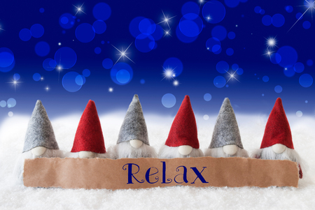 Label With English Text Relax. Christmas Greeting Card With Gnomes. Sparkling Bokeh And Blue Background With Snow And Stars. Stock Photo