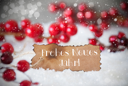 Burnt Label With German Text Frohes Neues Jahr Means Happy New Year. Red Christmas Decoration On Snow. Cement Wall As Background With Bokeh Effect And Snowflakes. Card For Seasons Greetings Stock Photo