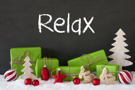 English Text Relax. Green Gifts Or Presents With Christmas Decoration Like Tree, Moose Or Red Christmas Tree Ball. Black Cement Wall As Background With Snow.