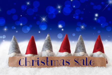 Label With English Text Christmas Sale. Christmas Greeting Card With Gnomes. Sparkling Bokeh And Blue Background With Snow And Stars.