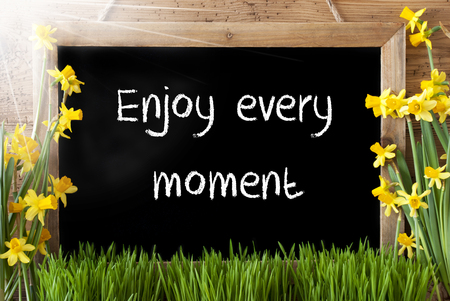 downtime: Blackboard With English Quote Enjoy Every Moment. Sunny Spring Flowers Nacissus Or Daffodil With Grass. Rustic Aged Wooden Background.