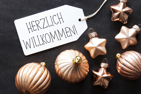 willkommen: Label With German Text Herzlich Willkommen Means Welcome. Bronze Christmas Tree Balls On Black Paper Background. Christmas Decoration Or Texture. Flat Lay View