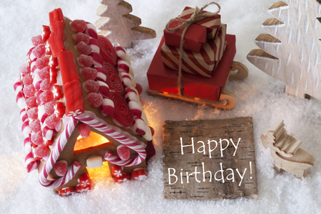 Label With English Text Happy Birthday. Gingerbread House On Snow With Christmas Decoration Like Trees And Moose. Sleigh With Christmas Gifts Or Presents.