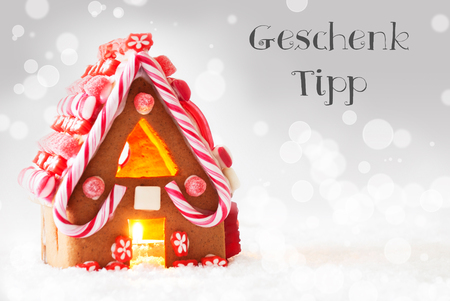 German Text Geschenk Tipp Means Gift Tip. Gingerbread House In Snowy Scenery As Christmas Decoration. Candlelight For Romantic Atmosphere. Silver Background With Bokeh Effect. Stock Photo