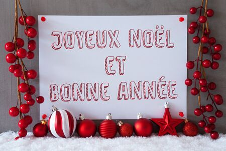 Label With French Text Joyeux Noel Et Bonne Annee Means Merry Christmas And Happy New Year. Red Christmas Decoration Like Balls On Snow. Urban And Modern Cement Wall As Background Stock Photo