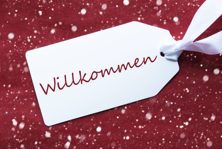 willkommen: One White Label On A Red Textured Background. Tag With Ribbon And Snowflakes. German Text Willkommen Means Welcome