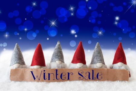 gnomos: Label With English Text Winter Sale. Christmas Greeting Card With Gnomes. Sparkling Bokeh And Blue Background With Snow And Stars.