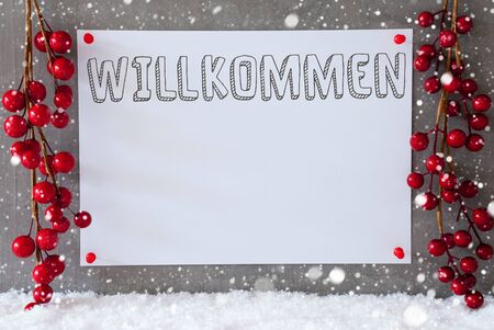willkommen: Label With German Text Willkommen Means Welcome. Red Christmas Decoration On Snow. Urban And Modern Cement Wall As Background With Snowflakes.