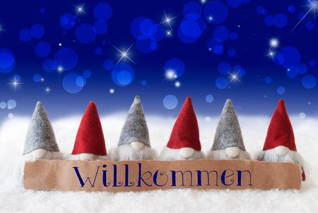 Label With German Text Willkommen Means Welcome. Christmas Greeting Card With Gnomes. Sparkling Bokeh And Blue Background With Snow And Stars.