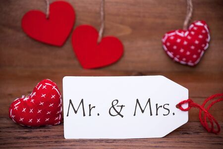 dona: Label With English Text Mr And Mrs. White Label With Red Textile Hearts. Retro Brown Wooden Background. Foto de archivo