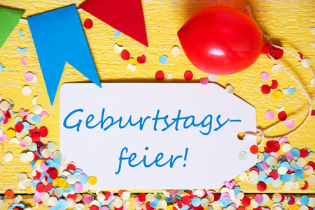 White Label With German Text Geburtstagsfeier Means Birthday Celebration. Close Up Of Party Decoration Like Streamer, Confetti And Balloon. Flat Lay Or Top View. Yellow Wooden Background