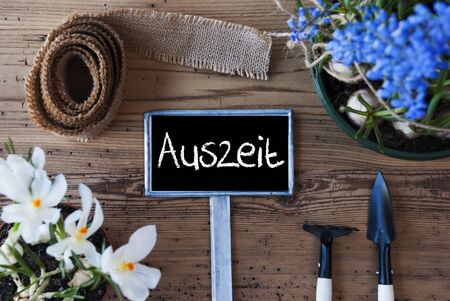 auszeit: Sign With German Text Auszeit Means Downtime. Spring Flowers Like Grape Hyacinth And Crocus. Gardening Tools Like Rake And Shovel. Hemp Fabric Ribbon. Aged Wooden Background