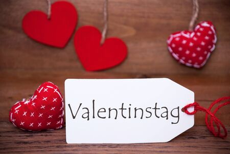 Label With German Text Valentinstag Means Valentines Day. White Label With  Red Textile Hearts.