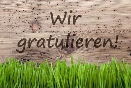 German Text Wir Gratulieren Means Congratulations. Spring Season Greeting Card. Bright Aged Wooden Background With Gras.