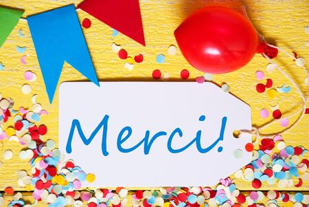 White Label With French Text Merci Means Thank You. Close Up Of Party Decoration Like Streamer, Confetti And Balloon. Flat Lay Or Top View. Yellow Wooden Background
