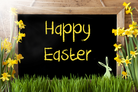 Blackboard With English Text Happy Easter. Sunny Spring Flowers Nacissus Or Daffodil With Grass And Easter Bunny. Rustic Aged Wooden Background.
