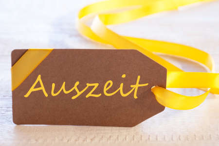 auszeit: Label With German Text Auszeit Means Downtime. White Wooden Background. Card For Seasons Greetings Or Easter Greetings