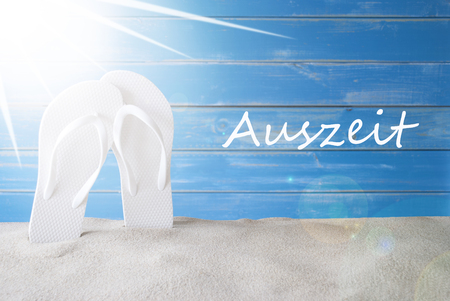 auszeit: German Text Auszeit Means Downtime. Sunny Summer Greeting Card With Sand And Flip Flops. Blue Vintage And Shabby Chic Wooden Background.