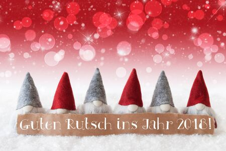 Label With German Text Guten Rutsch Ins Jahr 2018 Means Happy New Year 2018. Christmas Greeting Card With Red Gnomes. Sparkling Bokeh And Christmassy Background With Snow And Stars.