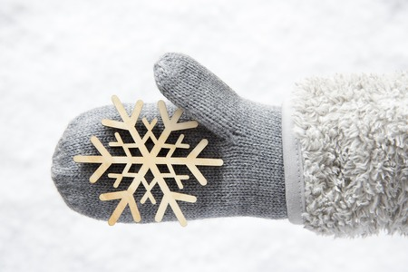 Wool Glove With A Wooden Snowflake, Snow Stock Photo