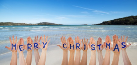 Many Hands Building Word Merry Christmas, Beach And Ocean Stock Photo