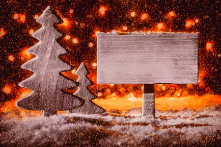 Wooden Sign With Copy Space For Advertisement. Christmas Tree On Snow And Fairy Lights In Background. Red Spotlight