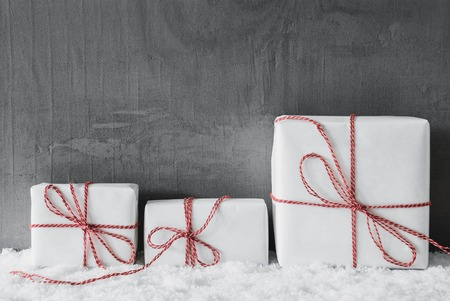 Three White Gifts With Red Ribbon. Grungy Cement Background With Snow.